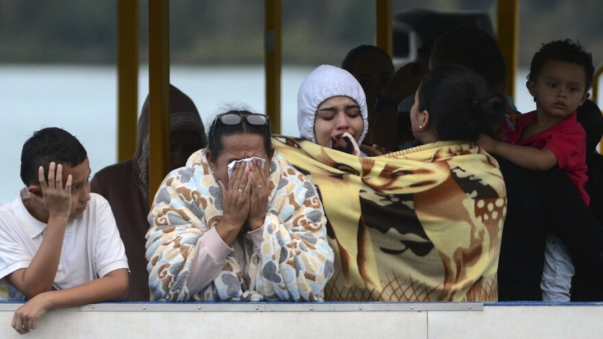 People who survived the capsizing of a ferry wait for more information about missing friends and relatives at a reservoir in Guatape, Colombia, on Sunday.