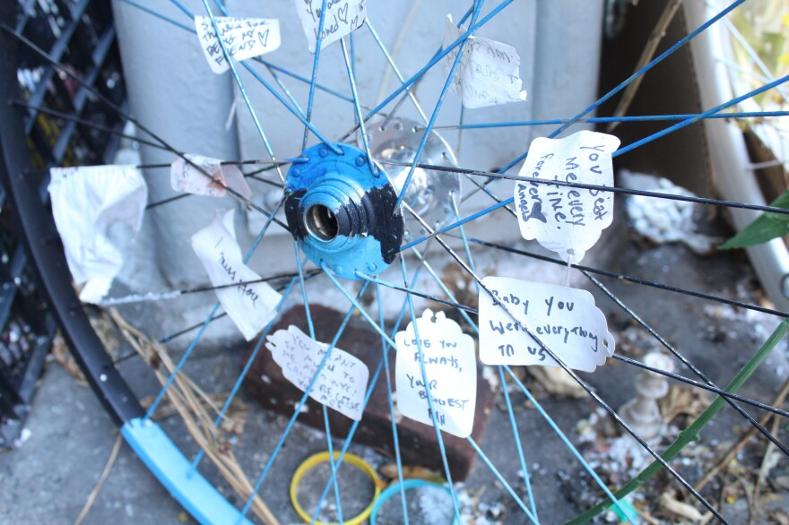 A memorial site in Manhattan, where Robyn Hightman, a bike messenger, was hit and killed by a truck this summer. People have tucked messages of support in the spokes of a bike wheel.