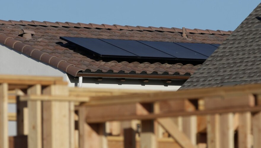 Solar panels are seen on the rooftop on a home in a new housing project.