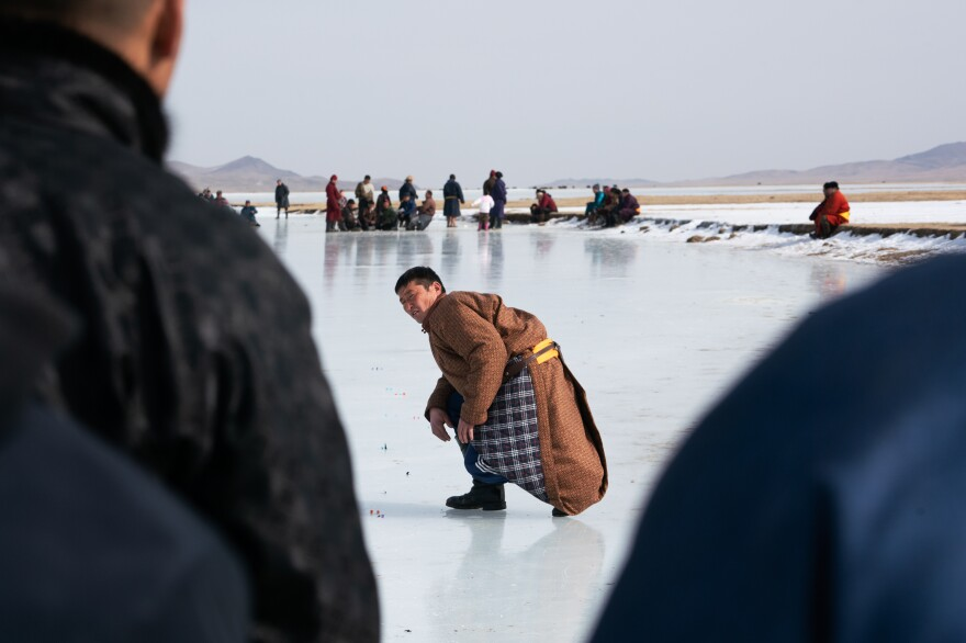 A competitor looks back at the crowd of spectators after sending his <em>zakh</em> down the ice toward the targets and the scorekeepers who stand behind them.