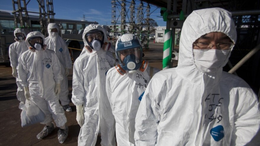Workers in protective suits and masks wait to enter the emergency operation center at the crippled Fukushima Dai-ichi nuclear power station on Nov. 12, 2011.