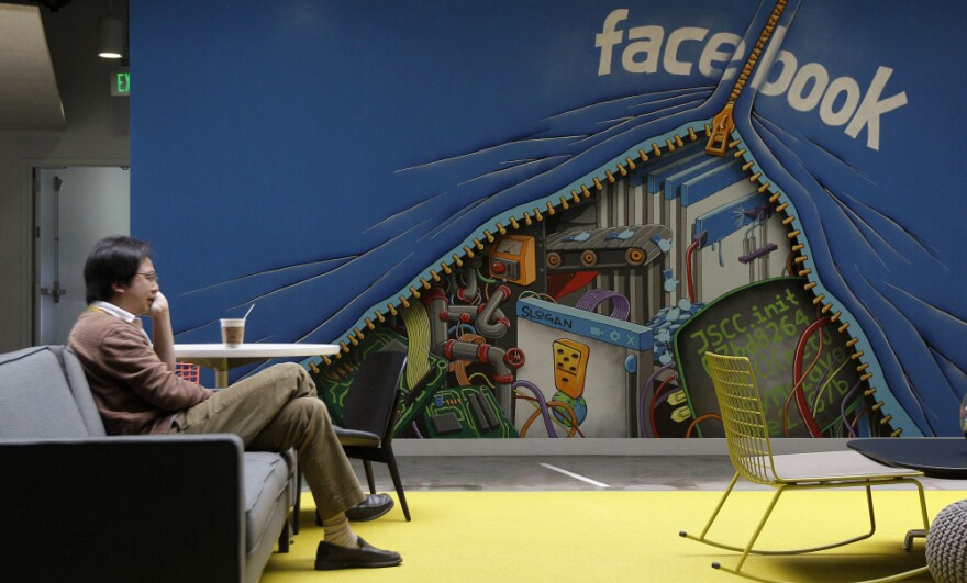 A worker sits in the Facebook office in Menlo Park, Calif. The amount of information Facebook learns about its users seems to have entranced Wall Street.