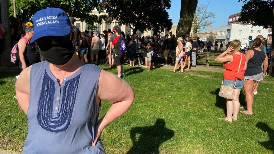 "Wearing a mask to protect herself from the coronavirus and a hat that reads ""Make Racism Wrong Again,"" Lydia Spottswood joins a protest in Kenosha, Wis., in response to George Floyd's killing by police. She thinks people are tired of President Trump's ""meanness."""