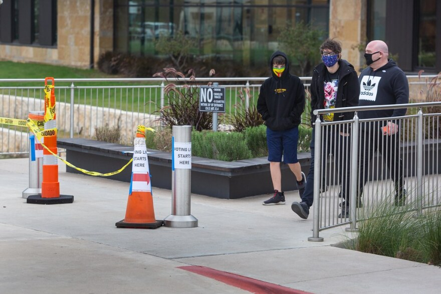 People wear masks while leaving an early voting site in Buda on Monday.