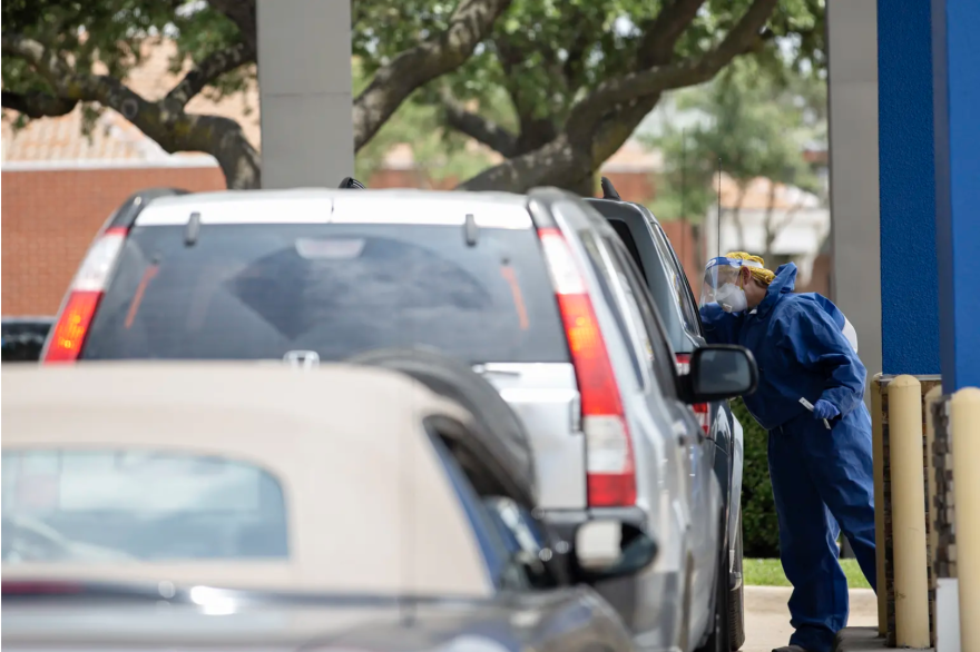 A health care worker administers a coronavirus test at a drive-thru testing site in Garland.