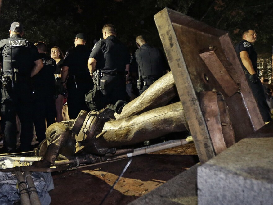 "Police stand guard after the Confederate statue known as ""Silent Sam"" was toppled by protesters on campus at the University of North Carolina in Chapel Hill, N.C., on Monday."