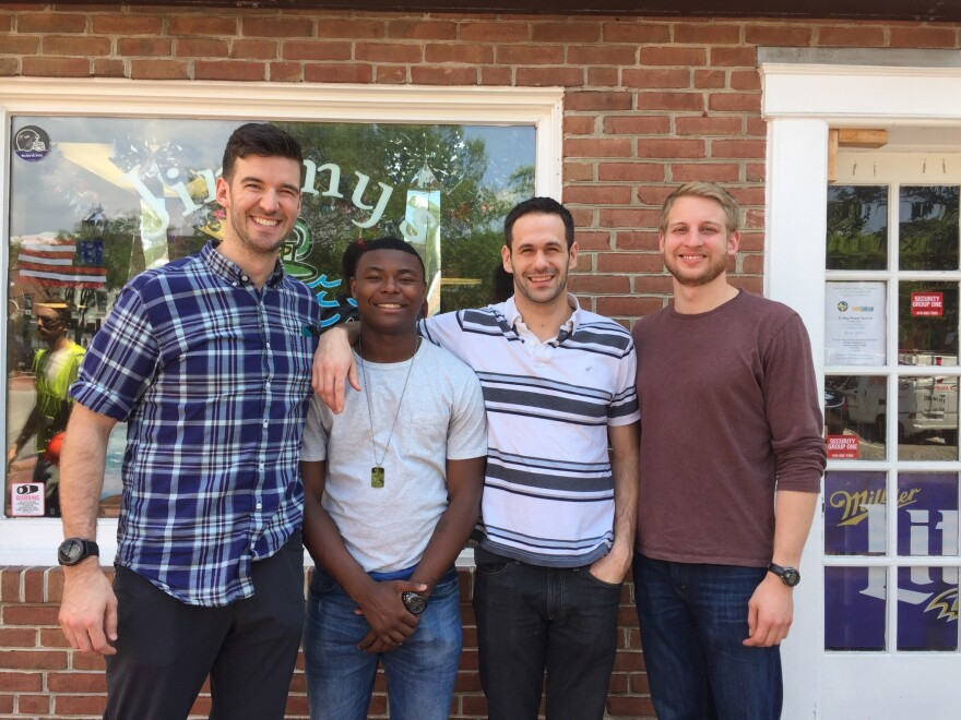Mentors Chris Regan, Jordan Wagner and Eric Schiffhauer pose for a picture with Jebree Christian, a recent high school graduate from West Baltimore, in front of Jimmy's on Baltimore's harbor.