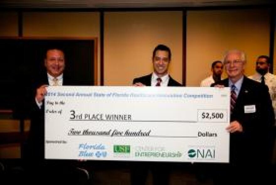 USF Biomedical Systems PhD student Simon Antonio Bello took 3rd place in the competition with his implantable device that measures intraocular pressure for glaucoma patients. He poses with his prize check between , David Pizzo, Market President of West Florida Florida Blue and Michael Fountain with the USF Center for Entrepreneurship.