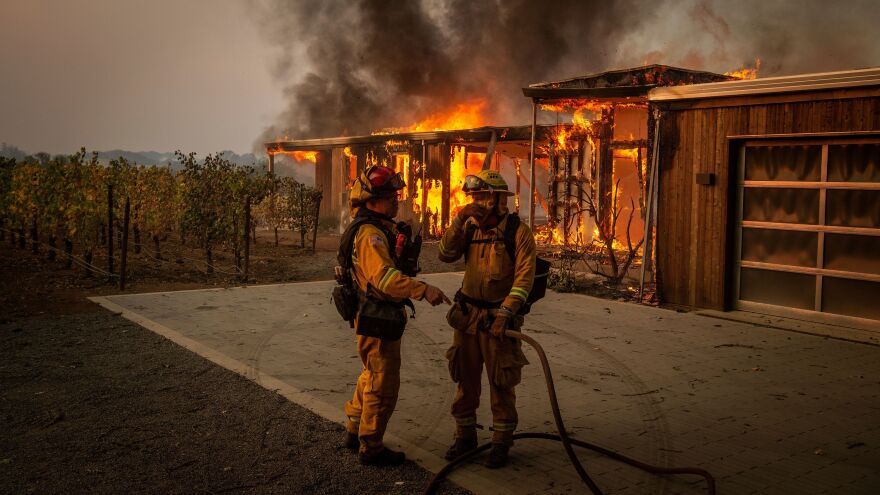 Firefighters discuss how to approach the scene Sunday as the Kincade Fire tears through Healdsburg, Calif. Powerful winds fanned the flames in Northern California, creating ideal conditions for the wildfire's spread.