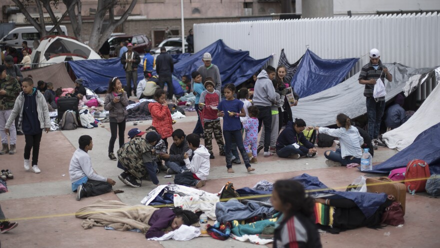 Migrants wait for access to request asylum in the U.S. at the El Chaparral border crossing point in Tijuana, Mexico, on Monday.