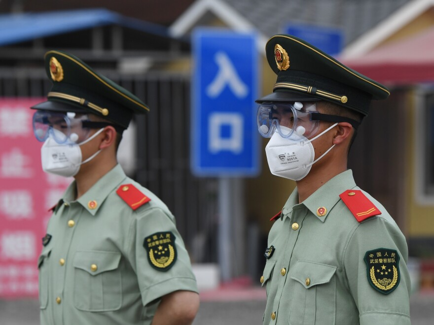 Paramilitary police officers wear face masks and goggles as they stand guard at an entrance to the closed Xinfadi market in Beijing on Saturday.