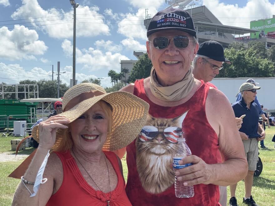 Woman in a hat and man in a cat T-shirt at a political rally