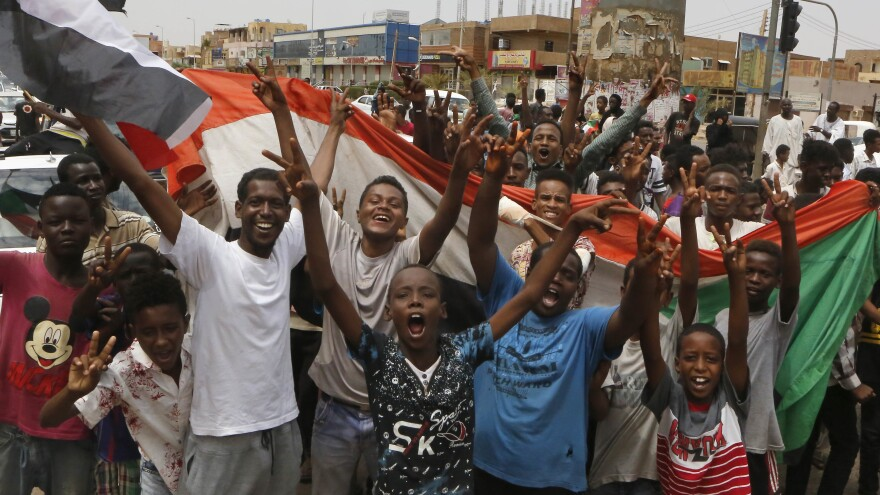 Sudanese celebrate in the streets of Khartoum on Friday after ruling generals and opposition leaders announced an agreement on a new governing body.