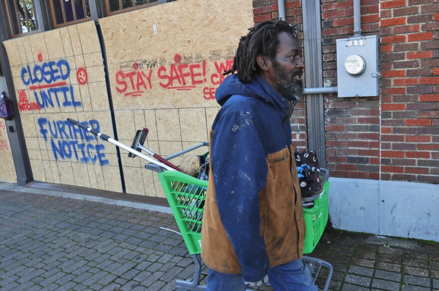 Vincent Amos, who identified himself as homeless, pulls a shopping cart with his belongings amid businesses closed by concerns of the COVID-19 coronavirus in the Deep Ellum section of Dallas. Amos said his shelter in place routine includes walking the area looking for work cleaning windows.