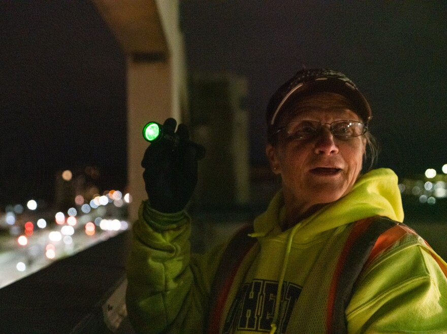 Sally Vehrenkamp stands with a green laser pointer, one of the tools she uses to chase crows from downtown Rochester, Minn. Members of the Crow Patrol also use distress crow calls and blank pistols to keep the birds from getting too comfortable.