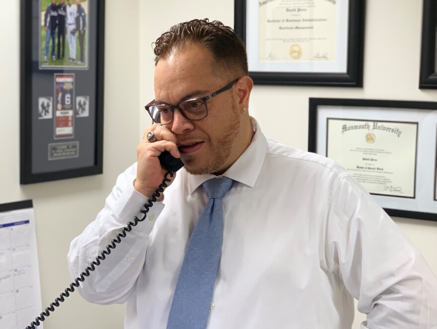 David Perez takes a call earlier this year in his office at the Long Branch Free Public Library. The U.S. Army veteran says he was surprised when his school advisers suggested he work there — but after several years in the job, he says it makes perfect sense.