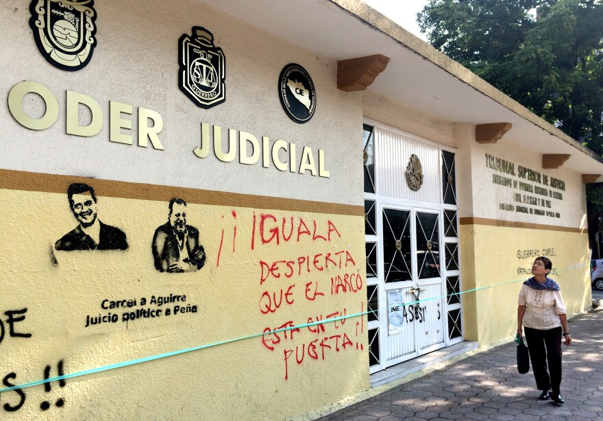 "Protesters have sprayed graffiti on the walls of Iguala's courthouse. Demanding jail time for Mexico's President Enrique Pena Nieto and the now-resigned governor of the state of Guerrero, demonstrators also sprayed ""Iguala wake up drug traffickers are at your door!"" They were referring to the mayor of Iguala."