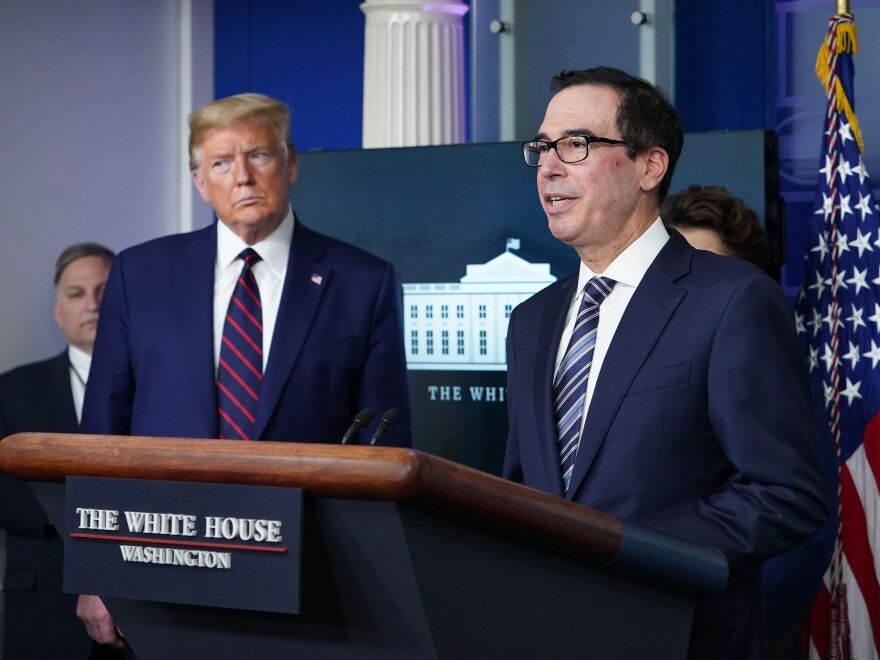Secretary of the Treasury Steve Mnuchin speaks while President Trump listens during Thursday's briefing from the White House coronavirus task force.
