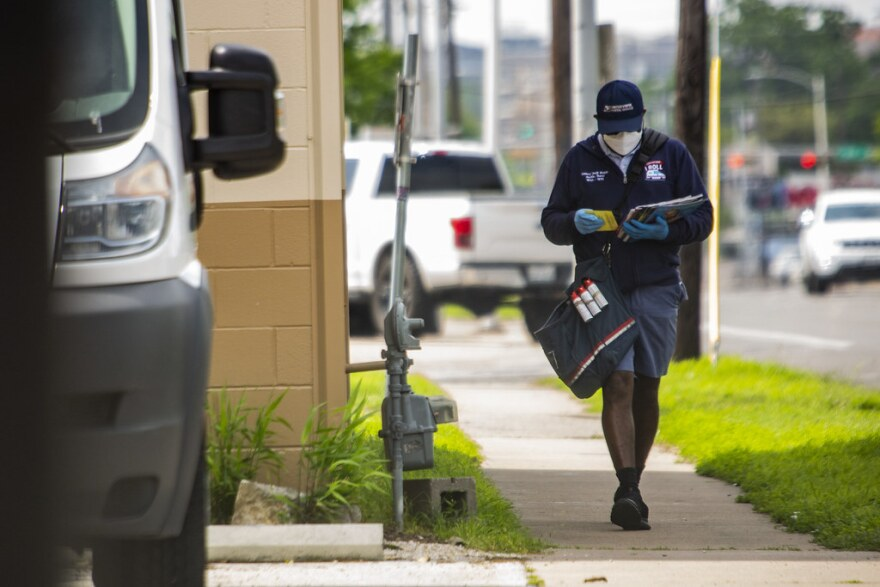 A mail carrier wears a mask and gloves while delivering mail in March.