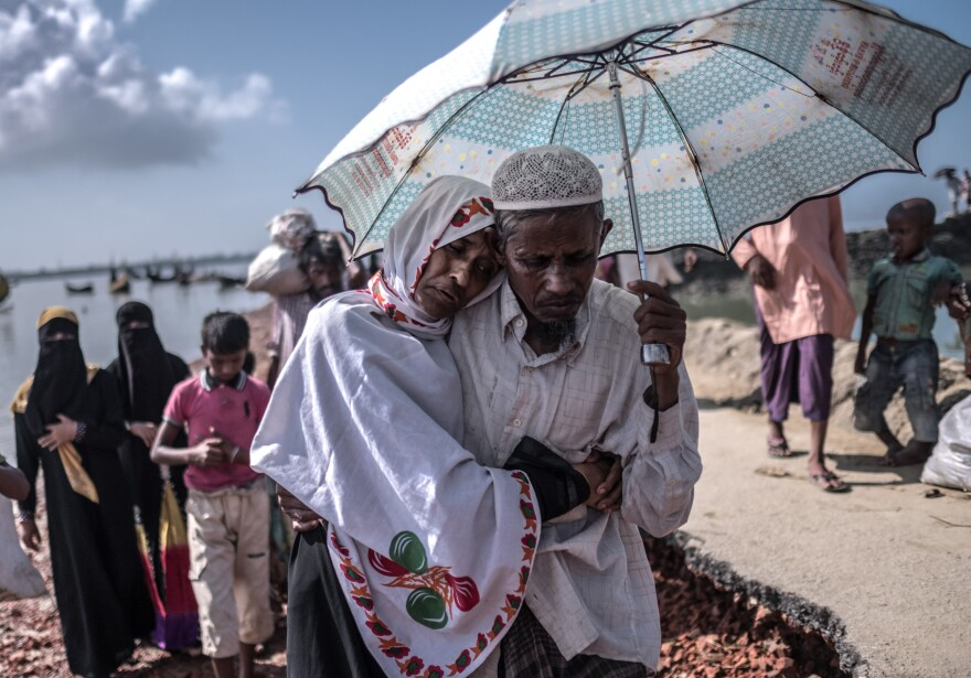 Nur Nahar, 40, a Rohingya refugee suffering from tuberculosis, clings to her husband, Bashir Ullah, 50, after arriving in Bangladesh.
