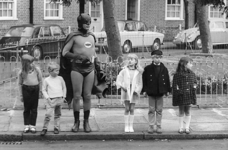 """""""What Batman provides, what all superheroes provide is this notion that good will triumph over evil,"""" says author Glen Weldon. """"That evil will have its day, but there will be somebody up there who will keep trying, who will keep looking out for us. ... He's catharsis in a cape."""" Above, Adam West, as Batman, makes a road safety film with child actors in Kensington, London in the late 1960s."""