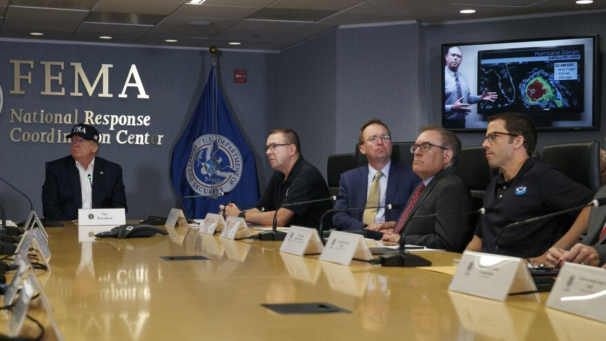 Acting NOAA head Neil Jacobs, seen here at far right as President Trump watches a briefing on Hurricane Dorian, is defending his agency's response to Trump's claim that Dorian had been predicted to hit Alabama hard.
