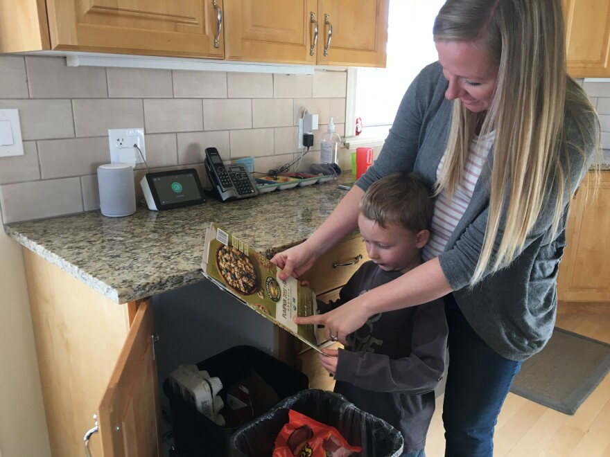 Photo of woman showing her son what is recyclable.