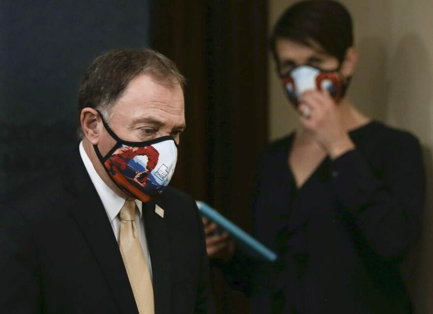 Photo of Gary Herbert wearing a mask and a yellow tie walking in front of Angela Dunn also wearing a mask