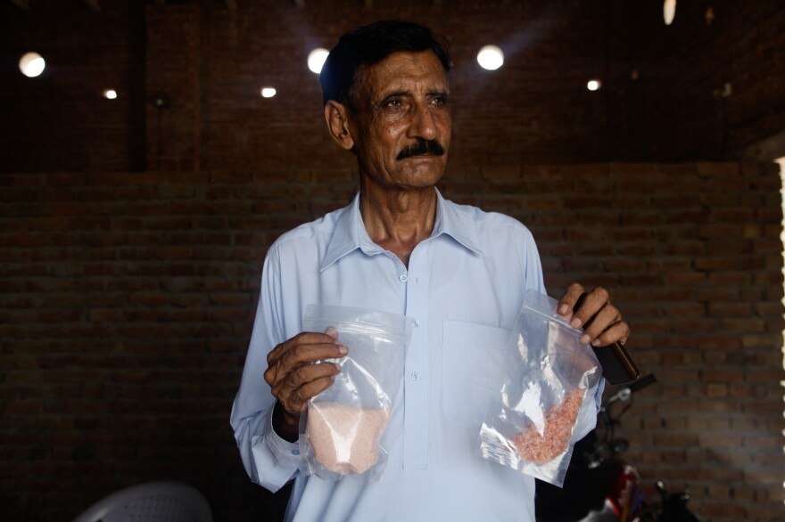 Qaisar Mahmood, a small-time Pakistani salt exporter, holds up two bags of pink Himalayan salt ground up to various consistencies. His business has been devastated by the ban on exports to India, and he says it is a bad idea to force companies to label salt as Pakistani, because the country is known as a place of troubles — not fancy salt.