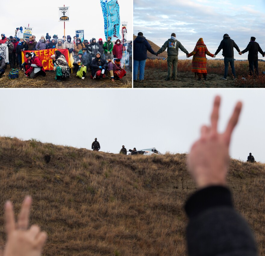 """Water protectors"" join hands in prayer during a peaceful protest as police line a hill on Turtle Island."