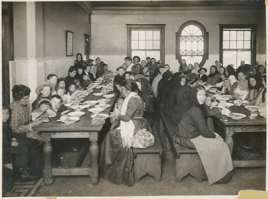 """An early-20th century photo by Edwin Levick, """"Uncle Sam, host. Immigrants being served a free meal at Ellis Island,"""" is part of the NYPL's photography collection."""