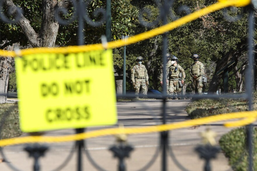"Law enforcement personnel can be seen behind the closed gate of the Texas Capitol grounds. A sign on the gate reads, ""Police line do not cross."