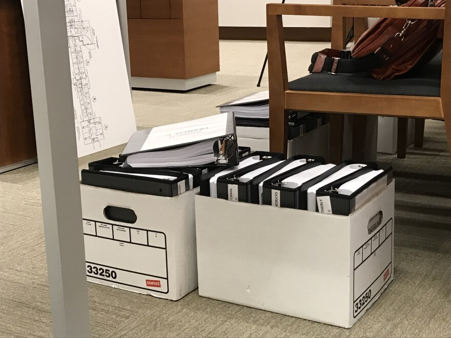 Boxes of evidence, notebooks, paperwork, and medical records fill the floors of the courtroom.