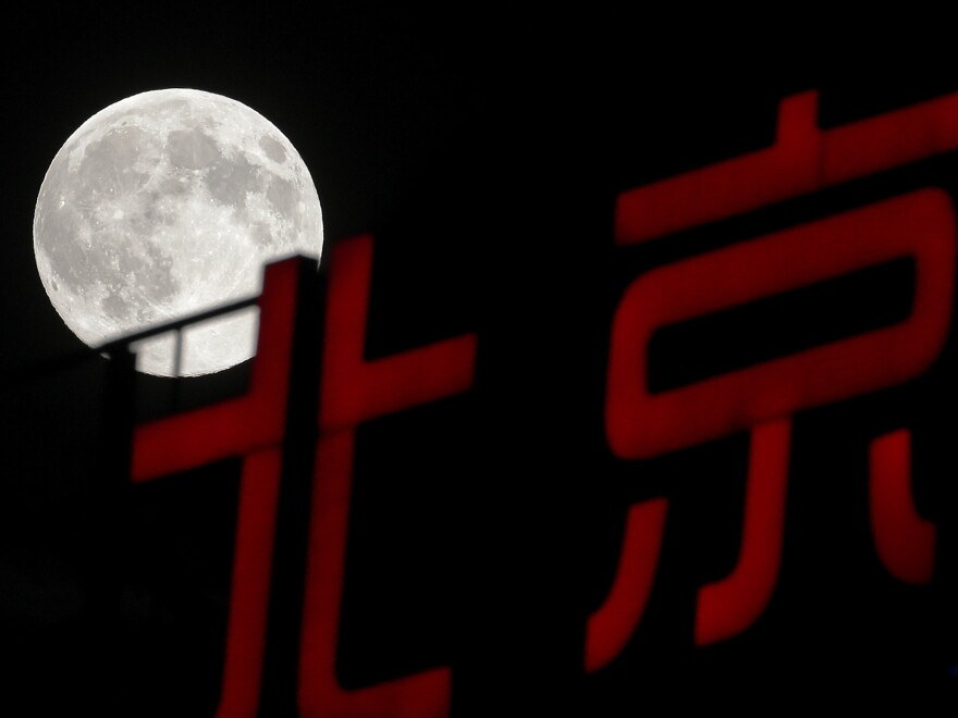 """The supermoon rises over Beijing on Sunday. The phenomenon, which scientists call a """"perigee moon,"""" occurs when the moon is near the horizon and appears larger and brighter than other full moons."""