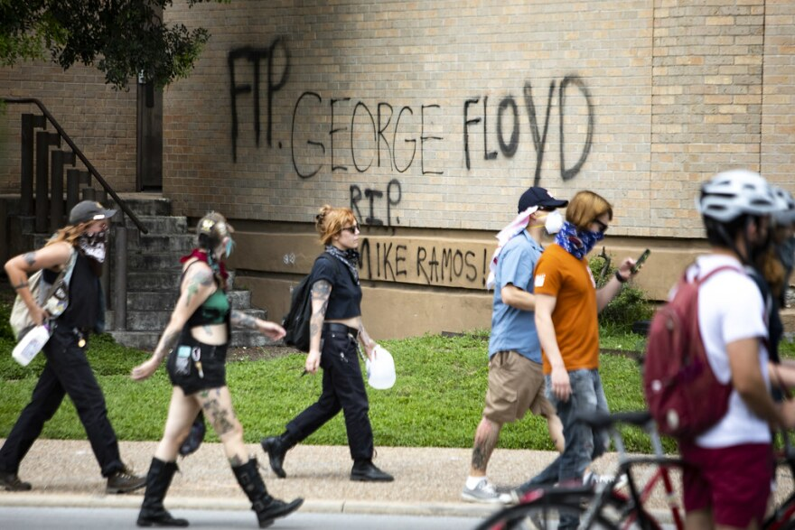 Graffiti on the side of Austin Police headquarters reads RIP George Floyd and Mike Ramos.