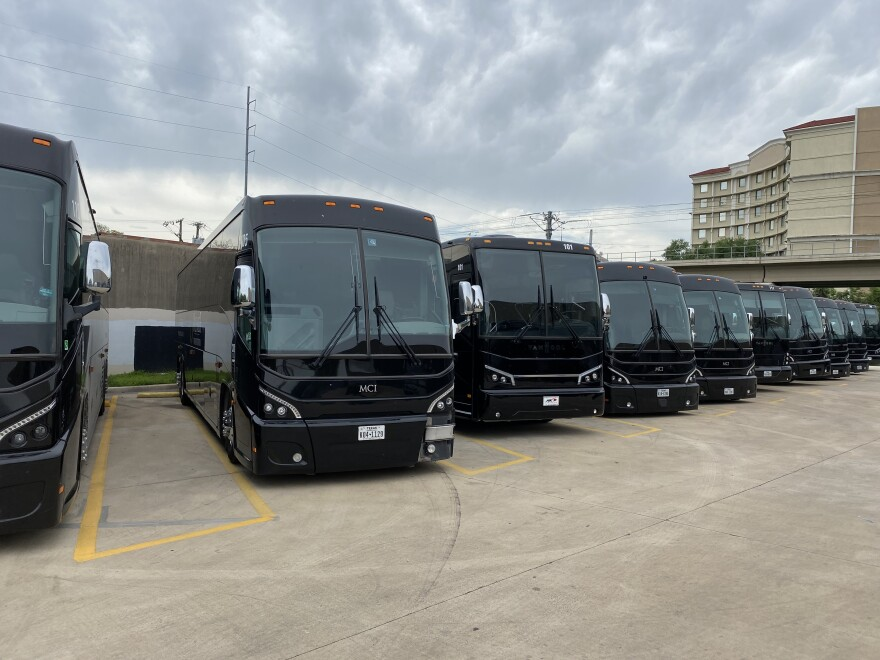 Premier Transportation's fleet of motor coaches sit in an empty parking lot. Each vehicle is worth more than a half-million dollars.