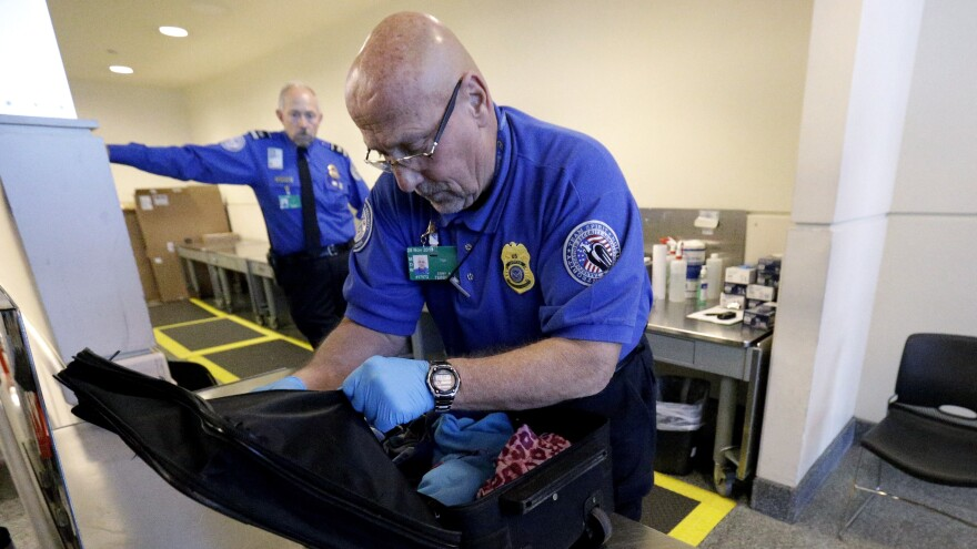 TSA agents, like this one at Chicago's Midway International Airport, discovered more than 2,000 firearms at the nation's airports last year — the overwhelming majority of them loaded, according to new data.