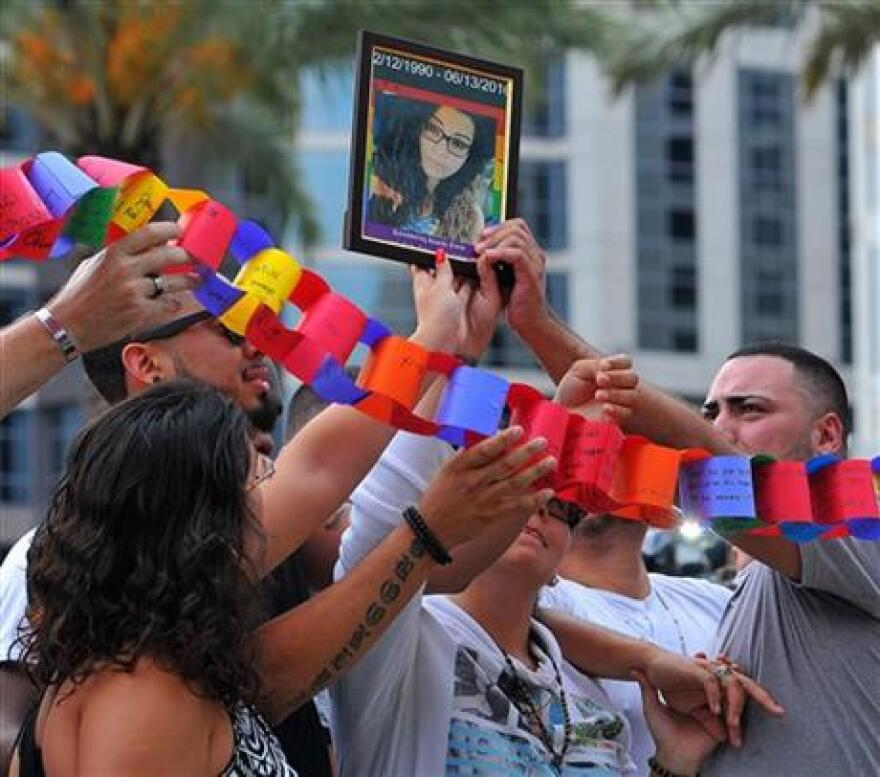 A portrait of Amanda Alvear, one of the people killed in the Pulse nightclub in Orlando, Fla., early Sunday, is held up over the crowd during a vigil honoring the victims of a mass shooting.
