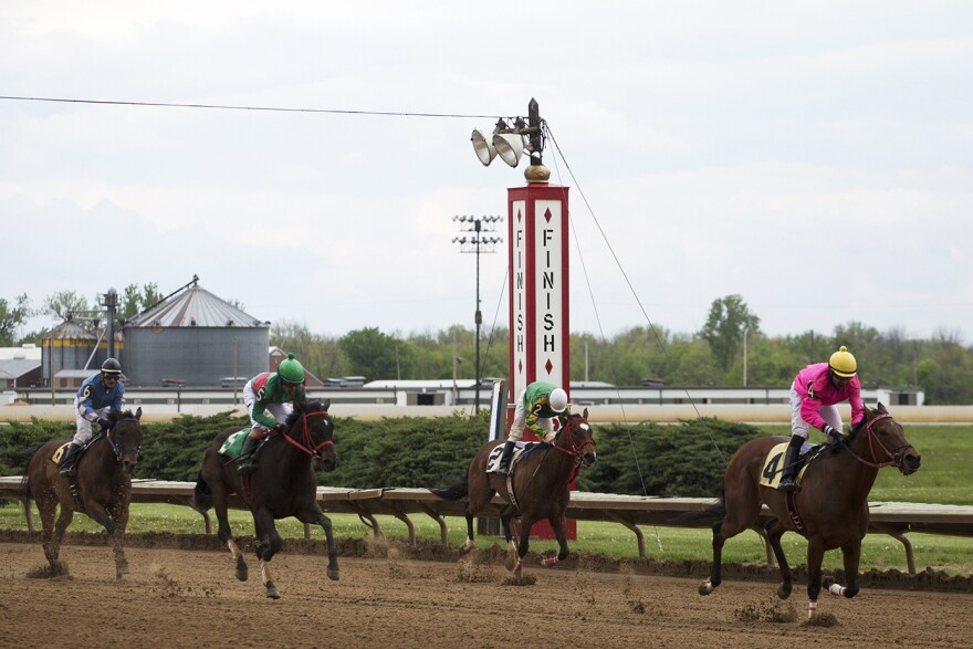 Jockeys cross the finish line as they complete the first race of opening day.