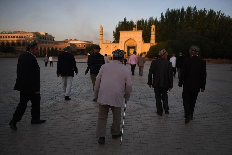 Uighur men walk towards the Id Kah mosque to attend prayers marking the end of Ramadan, in Kashgar in China's northwest Xinjiang region, in 2019.