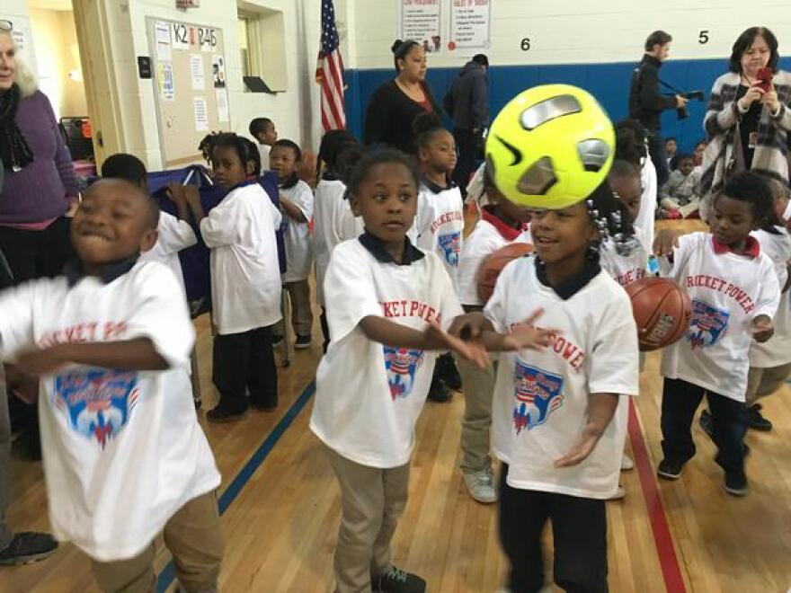 Students at J.W. Ray Learning Center in Old East Dallas play with new balls donated by Looney and Associates. The firm also bought the school a new washer and dryer.