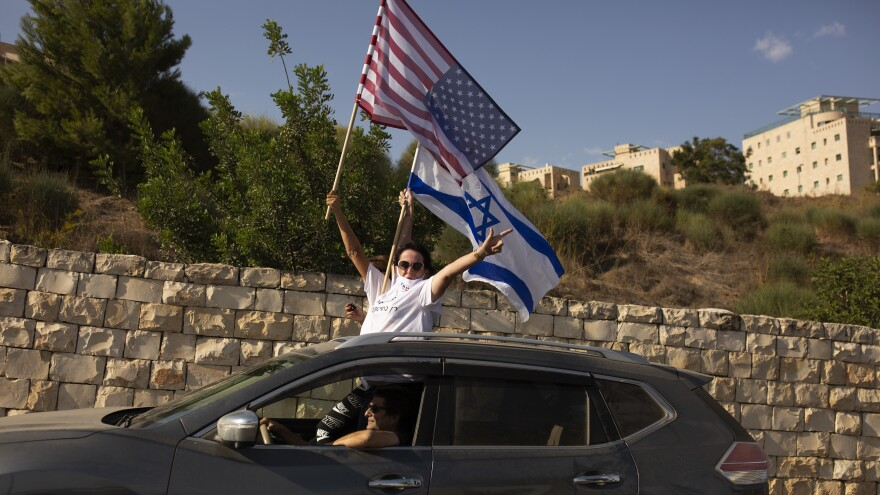 Supporters of President Trump wave U.S. and Israeli flags from a car headed for a rally outside the U.S. Embassy in Jerusalem, Oct. 27.