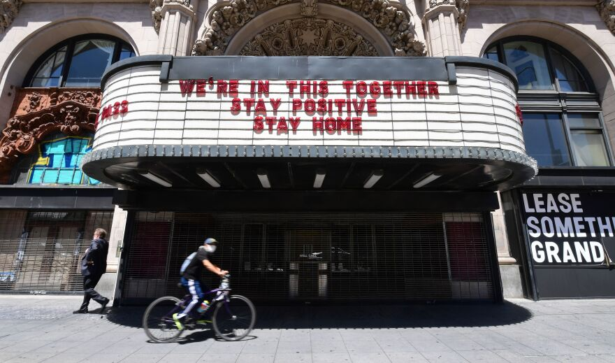 A cyclist in a face mask rides past the Million Dollar Theater in downtown Los Angeles on Monday. Gov. Gavin Newsom announced that California — amid encouraging coronavirus benchmarks — will allow some retail businesses to reopen with modifications as early as Friday.