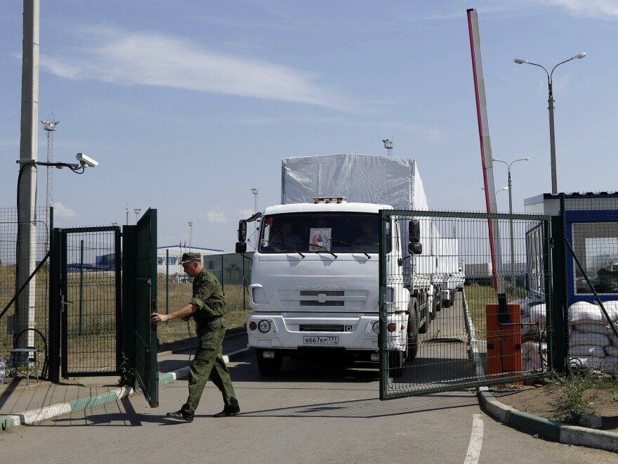 A Russian border guard opens a gate into Ukraine for the first trucks from the Russian town of Donetsk, Rostov-on-Don region, on Friday. The convoy had been stalled near the border for more than a week.