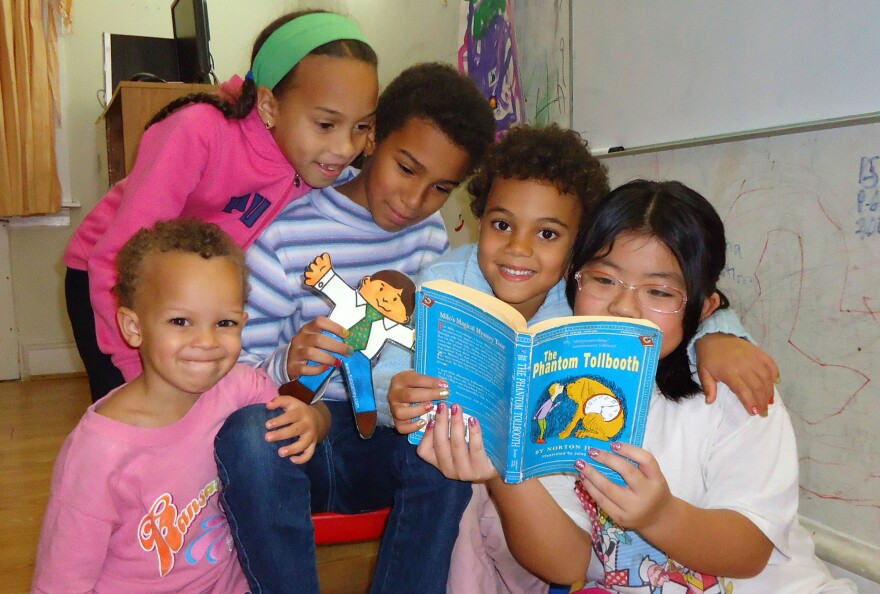 Carina Jaffe, 3; Larissa Jaffe, 9; Denali Jaffe, 10; Zahra Jaffe, 6; and their friend Christina Tonnu, 8, read <em>The Phantom Tollbooth</em> together in Philadelphia.