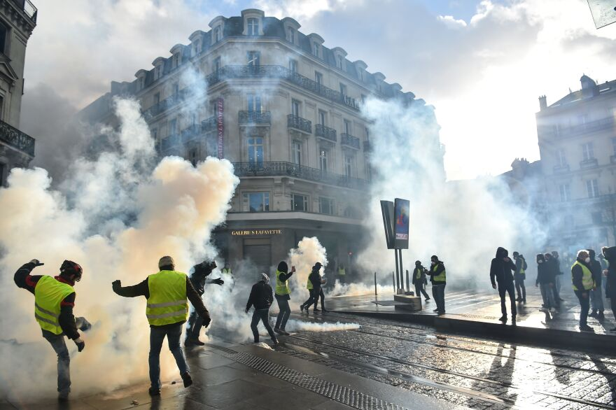 Protesters clash with police as tear gas is used during an antigovernment demonstration called by the yellow vests in Angers, in western France, on Jan. 19.