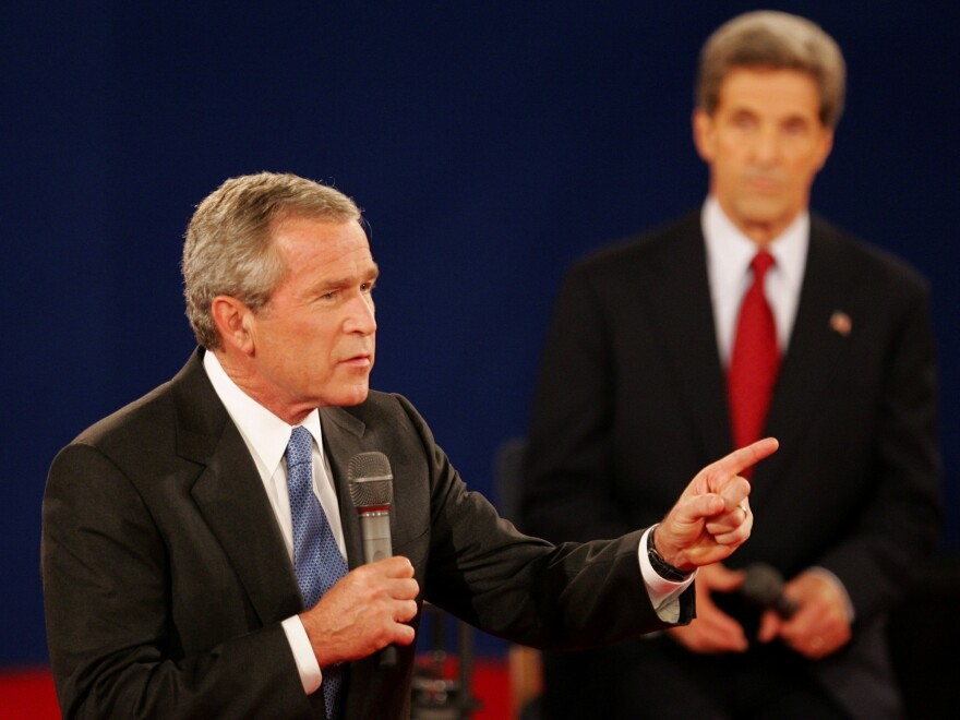 """In a 2004 debate in St. Louis, President Bush answers a question as his opponent, Sen. John Kerry, listens. Both candidates used a number of """"pivots"""" in their debates."""