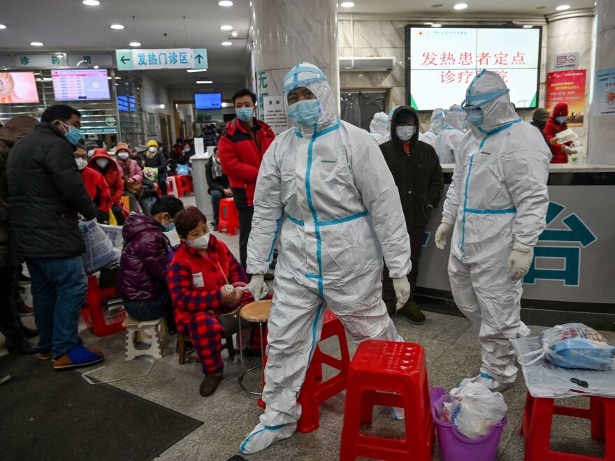 A scene from January 25, 2020, in Wuhan: Health workers in protective garb walk next to patients awaiting medical attention at the Wuhan Red Cross Hospital.