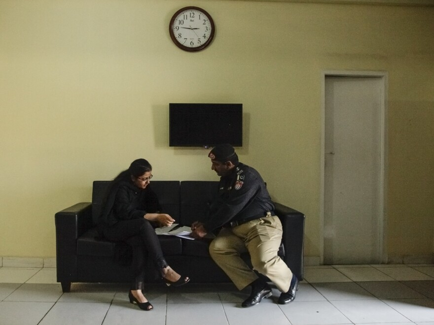 Police superintendent Suhai Talpur discusses work with a colleague in her office at the Clifton police station in Karachi.