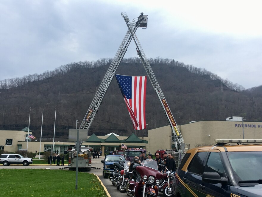 Fire ladder trucks are shown outside Riverside High School during the funeral for Pratt Volunteer Fire Department Lt. Tom Craigo in Belle, W.Va., Tuesday, April 3, 2018.